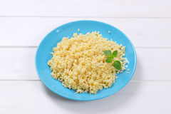 Cooked pearl barley. Cooked whole groats on blue plate Royalty Free Stock Images