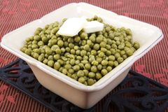 Cooked peas with butter in a ceramic dish stock photo