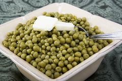 Cooked peas with butter in a ceramic dish Stock Photos
