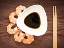 Cooked peeled king prawns, white bowl with soy sauce and wooden chopsticks on a brown wooden background. Delicacy, tasty and royalty free stock image