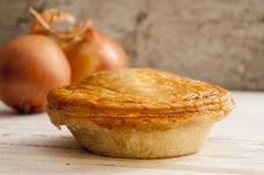 Cooked Pie and a Pair of Onions Royalty Free Stock Images