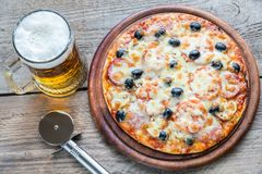 Cooked pizza with a glass of beer Stock Photos