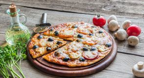 Cooked pizza on the wooden board Stock Photos