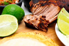Cooked Pork Carnitas. Pork Carnitas pulled apart ready to make tacos with fresh sliced lime Stock Image