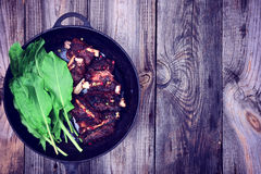 Cooked pork ribs in a beer on a black cast-iron frying pan Royalty Free Stock Photography
