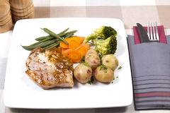 Cooked pork steak and vegetables Stock Image
