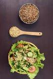 Cooked porridge. Fresh vegetable salad. Prospects buckwheat. Dark background. Wooden spoon Royalty Free Stock Photography