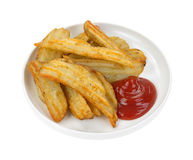 Cooked potato wedges in dish with ketchup Stock Images