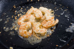 Cooked prawns and garlic in skillet Stock Photography