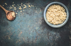 Cooked quinoa in blue bowl with cooking wooden spoon on dark rustic background, top view, place for text: recipes and menus, horiz Royalty Free Stock Photography