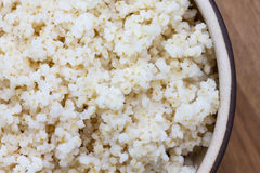 Cooked quinoa in a ceramic bowl on wood Royalty Free Stock Images