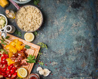 Cooked quinoa in cooking pot with fresh ingredients for salad making on dark rustic background, top view Royalty Free Stock Photo
