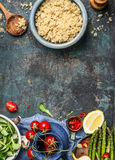 Cooked quinoa with wooden spoon and cooking ingredients on dark rustic background, top view Stock Photos