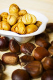 Cooked and raw chestnut. Fruit in white bowl royalty free stock photos