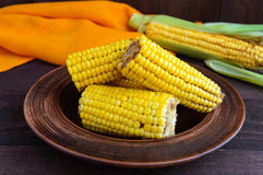 Cooked and raw corncobs on a dark wooden background Royalty Free Stock Photo