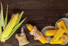 Cooked and raw corncobs on a dark wooden background. Royalty Free Stock Image