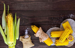 Cooked and raw corncobs on a dark wooden background Royalty Free Stock Photography