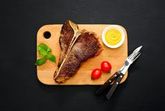 T-bone steak served and ready to eat. Cooked and ready to eat T-bone steak served on a board, flat lay, view from above Stock Photography