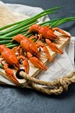 Cooked red river crayfish on a wooden chopping Board. Black background, top view. stock photo