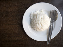 Cooked rice in bowl with spoon and dishcloth on old wooden table . Stock Photo