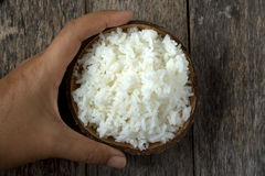 Cooked rice in coconut bowl with hand Royalty Free Stock Photo