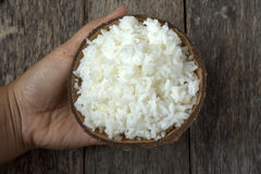 Cooked rice in coconut bowl with hand Royalty Free Stock Photography