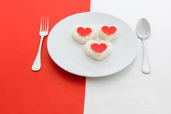 Cooked rice heart shapes with a spoon and fork on white dish Stock Photo