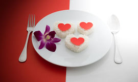 Cooked rice heart shapes with a spoon and fork on white dish and Stock Photography