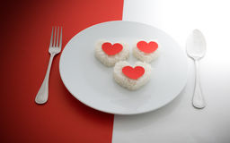 Cooked rice heart shapes with a spoon and fork on white dish Royalty Free Stock Photos