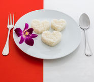Cooked rice heart shapes with a spoon and fork on white dish and Royalty Free Stock Images