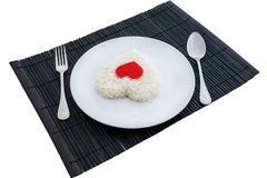 Cooked rice heart shapes with a spoon and fork on white dish Stock Image