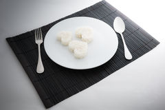 Cooked rice heart shapes with a spoon and fork on white dish Stock Images
