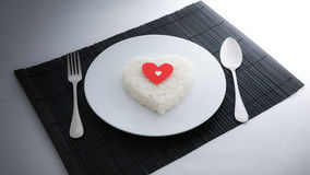 Cooked rice heart shapes with a spoon and fork on white dish Royalty Free Stock Photo