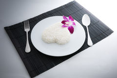Cooked rice heart shapes with a spoon and fork on white dish and Royalty Free Stock Photo