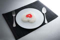 Cooked rice heart shapes with a spoon and fork on white dish Stock Photos