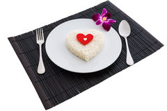 Cooked rice heart shapes with a spoon and fork on white dish and Stock Photo