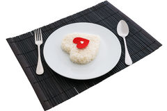 Cooked rice heart shapes with a spoon and fork on white dish Royalty Free Stock Images