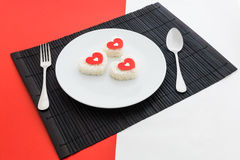 Cooked rice heart shapes with a spoon and fork on white dish Stock Photography