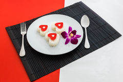 Cooked rice heart shapes with a spoon and fork on white dish and Stock Image