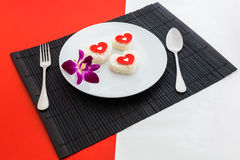 Cooked rice heart shapes with a spoon and fork on white dish and Stock Photos