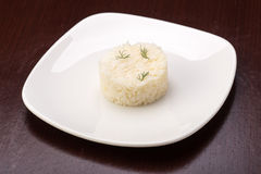 Cooked rice. On the plate on wooden table Stock Photo