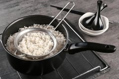 Cooked rice in saucepan with sifter. On grate Stock Photography