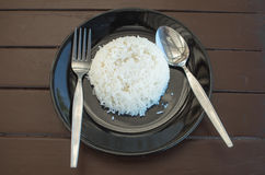 Cooked rice and spoon. In plate Royalty Free Stock Photos