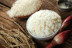 Cooked rice, uncooked rice and paddy rice on wooden tabel Stock Photos