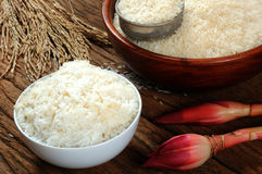 Cooked rice, uncooked rice and paddy rice on wooden table Stock Images