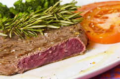 Cooked rump steak. On plate with a rosemary stick and tomato Royalty Free Stock Image