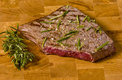 Cooked rump steak. On wooden board with a rosemary stick Royalty Free Stock Images