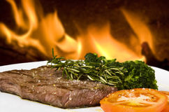 Cooked rump steak. On white plate with tomato and rosemary Royalty Free Stock Photography