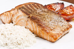 Cooked salmon. Fillet on white plate with rice and tomato Stock Images