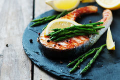 Cooked salmon with asparagus and lemon. Selective focus Royalty Free Stock Image